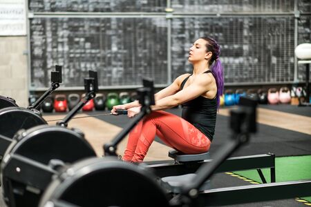 Young woman working out exercising on a rowing machine inside a professional gym during training in a health and fitness concept viewed from behind a row of machines