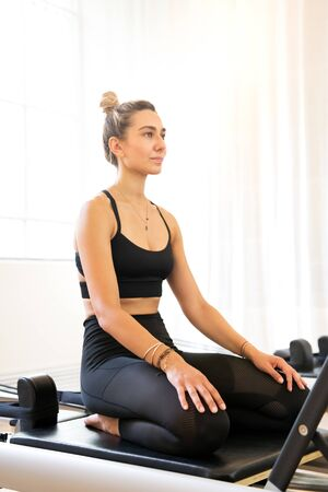 Fit woman sitting on pilates reformer bed before exercises at gym