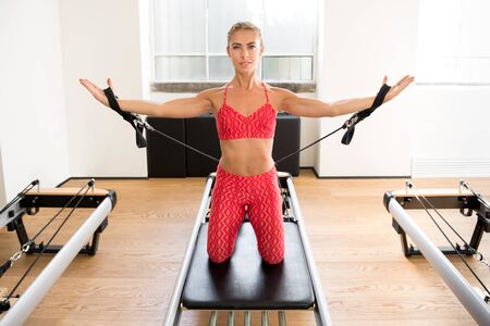 Woman doing pilates arm work with resistance straps on a reformer bed to strengthen and tone her muscles in a health and fitness concept