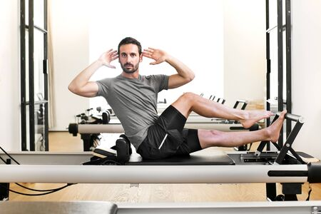 Man performing a pilates single leg stretch exercise on a reformer bed in a gym twisting to face the camera to stretch and tone the abdominal muscles Stock Photo