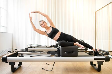 Woman performing a pilates yoga mermaid exercise or side stretch to tone the intercostal muscles on a reformer bed in a gym