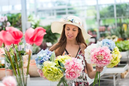 Young woman choosing a bunch of fresh cut hydrangeas in pink, white, green and blue in a nursery holding them in her hands as she makes her choice for purchase