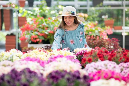 Young woman in sunhat buying colorful flowering summer plants at a nursery making a selection from a large array on display