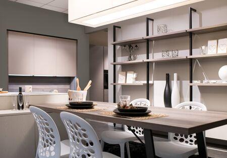 Cocina y comedor de planta abierta con decoración beige neutro, unidad de pared con estantes y una mesa y sillas modernas iluminadas por una gran luz de techo
