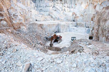 Koparka lub koparka wewnątrz odkrywki do wydobywania białego marmuru z Carrary przedstawiająca duże bloki kamienia wycięte ze zbocza góry w Toskanii we Włoszech Zdjęcie Seryjne