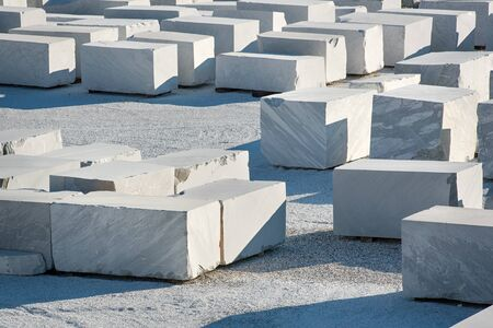 Many large rectangular blocks of white Carrara marble outdoors at a mine or quarry in Tuscany, Italy, in a concept of mining of natural resources for construction and sculpture