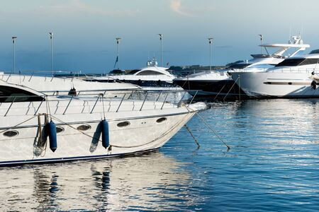 Luxury motorboats or yachts moored in a marine harbor or marina reflected in the sheltered sunlit water