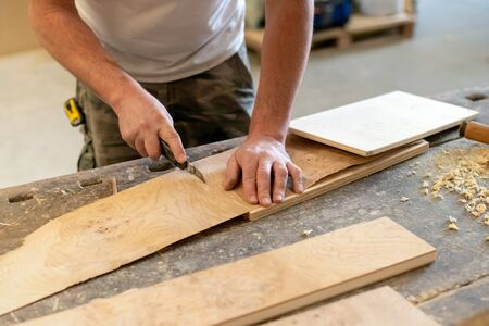 Carpenter cutting a wooden briar root sheet for use as a veneer using a small blade in a woodworking workshop in a close up on his hands
