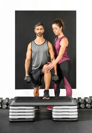 Female personal trainer assisting a man in a gym to do step ups while holding two dumbbell weights in a health and fitness concept