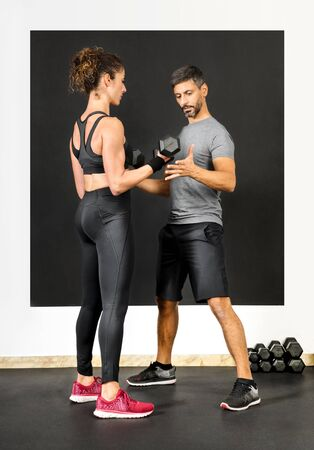 Male personal training assisting a woman with dumbbell weights in a gym as she works out strengthening her muscles in a health and fitness concept