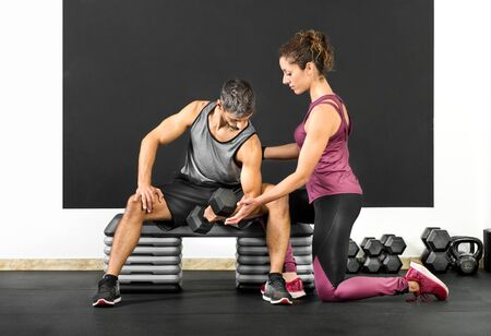 Female fitness trainer helping a man in a gym to do curls using a dumbbell weight to strengthen his biceps in a health and fitness concept