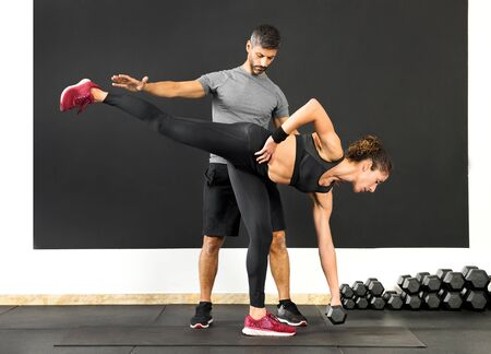 Athletic woman doing a single leg deadlift using a dumbbell weight assisted by a male personal trainer in a gym in a health and fitness concept