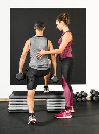 Female personal trainer in a gym assisting a man lifting dumbbell weights with step ups viewed from the rear in a health and fitness concept