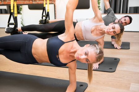 Gym class of women and a man doing suspended elbow side plank Trx exercises to strengthen core muscles in a close up view on mats in a health and fitness concept
