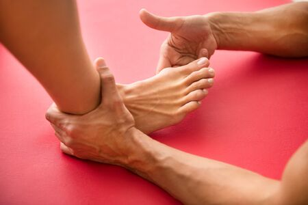 Osteopath assessing a hallux valgus or bone growth at the base of the big toe on a woman patient in a close up on her foot