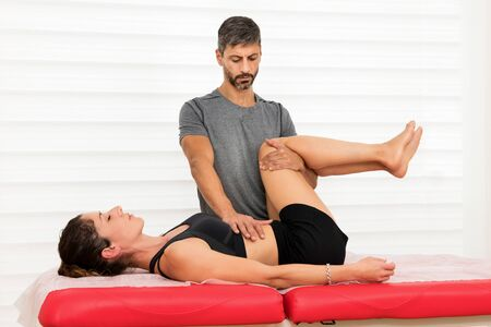 Osteopath performing a lumbar mobilization treatment to align the vertebrae of the spine on a young woman in an alternative medicine and healthcare concept