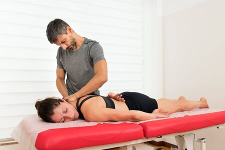 Male osteopath doctor practicing myofascial trapezius treatment, massaging his woman client muscles, while she laying on her belly on a couch Фото со стока