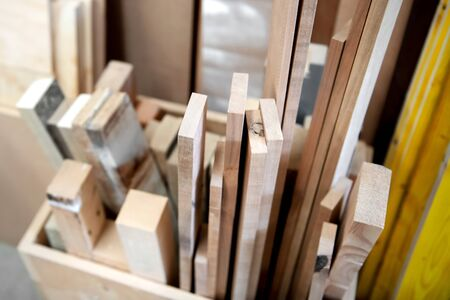 Assorted spare blocks and planks of wood stored in a box in a woodworking or carpentry workshop in a close up view Stockfoto