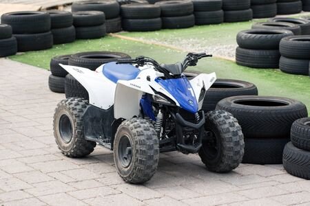 Kids quad bike parked on a track or circuit between protective safety tyres outdoors in sunshine conceptual of recreational sport