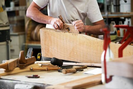 Carpenter planing a block of wood with a planer to smooth the edge in a woodworking workshop in a close up on tools on the bench, his hands and shavings