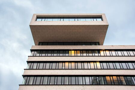Architecture design of modern office building with balcony on the top, viewed from low angle against cloudy sky