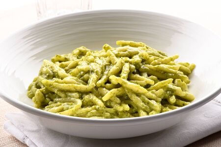 Trofie al pesto, a regional small twisted pasta strip with a pesto sauce, from the Liguria region of Italy in close up in a white bowl
