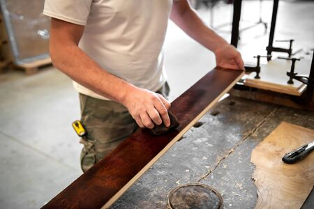Carpenter or woodworker staining or coloring a briar root panel in a close up on the plank of wood and his hands over the workbench