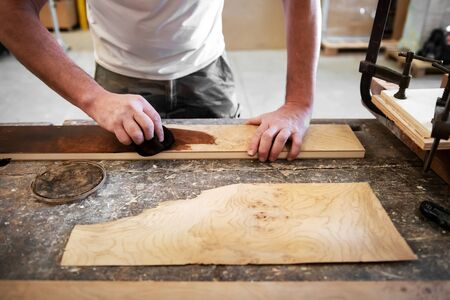 Carpenter applying wood stain to a briar root panel on a workbench in a woodworking workshop in a low angle view of his hands as he works