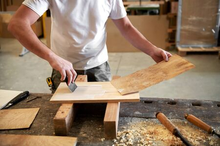 Carpenter applying glue to attach a panel of briar root veneer to a block of wood in a woodworking factory or workshop during manufacturing Archivio Fotografico