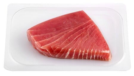 Vacuum packed tuna fillet piece in transparent plastic viewed in close-up isolated on white background. Food packaging for preserving the freshness and displaying the quality of the product concept
