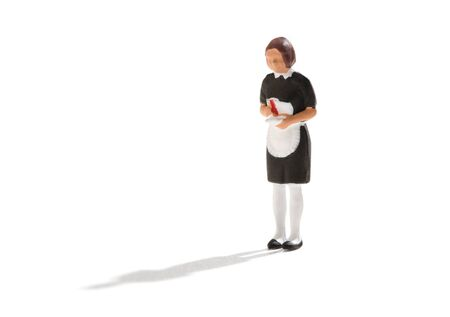Miniature figure of a maid or hired help in a black uniform with white apron over a white background with copy space