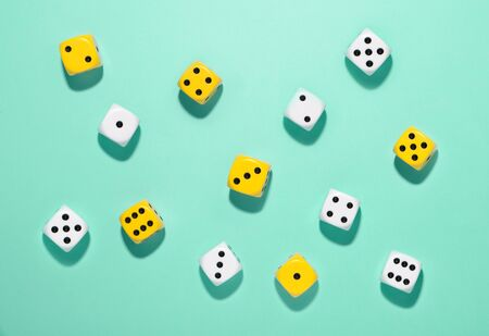 Top view of randomly scattered yellow and white dice on a green background with shadows in an indoor games and gambling concept viewed from above
