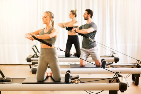 Group of two women and a man doing torsion rotation exercises during a class using pilates reformer beds in a high key gym with copy space in an active lifestyle and fitness concept Stock Photo