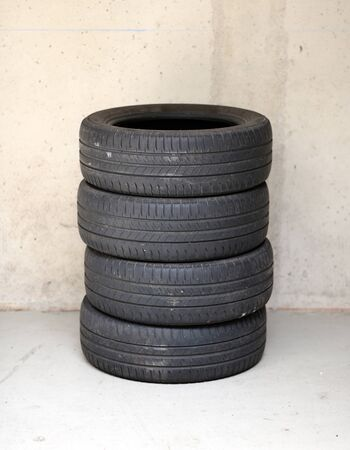 Set of four stacked used car or motor vehicle tires on a concrete floor against a wall with copy space