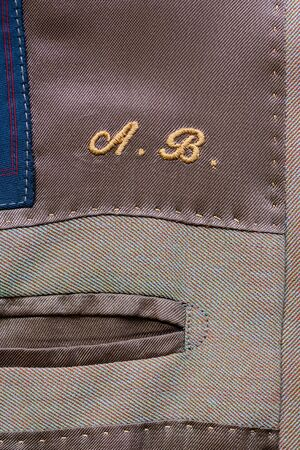 Initials embroidered inside a bespoke garment in yellow thread above an inside pocket in close up on the textile