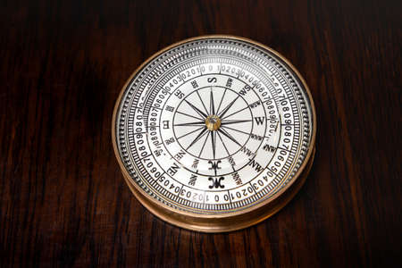 Old round brass magnetic vintage compass with glass dial lying on a wooden board in a high angle view
