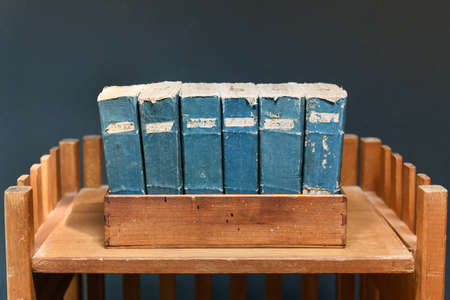 Set of old worn and tattered vintage books with blue spines and labels on a wooden shelf against a gray wall