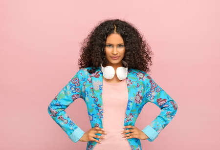 Fashionable young Afro American girl in a bespoke tailored floral blue jacket with headphones around her neck standing with hands on hips against a pink studio background Archivio Fotografico