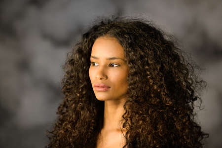 Headshot of a beautiful thoughtful black girl with long curly hair looking off to the side with a pensive serious expression