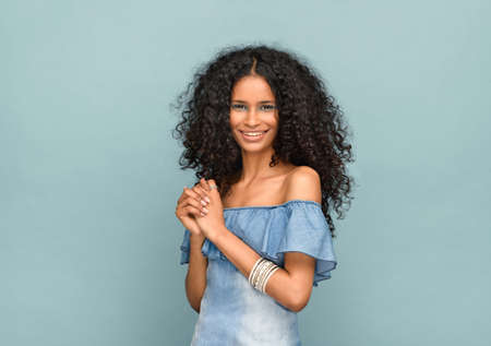 Studio portrait of a beautiful slender black girl with gorgeous curly long hair looking at the camera with a beaming warm friendly smile against a blue background Imagens