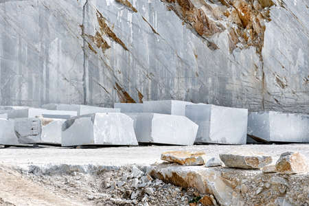 Blocks of cut white Carrara marble in the quarry in front of the rock face ready for transportation in Tuscany Italy