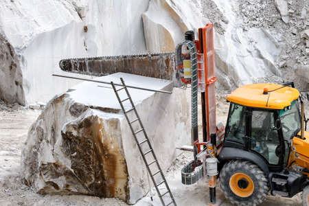 Heavy duty saw attached to a tractor for mobility for cutting blocks of white Carrara marble in an open cast mine or quarry in Tuscany, Italy Banque d'images