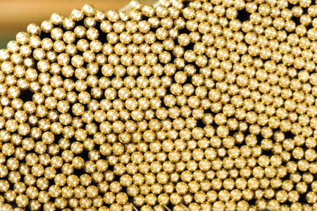 Background texture of the machined ends of brass rods packed tightly together in a warehouse or factory in a full frame view