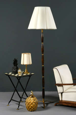 Interior decor with stylish vintage furniture comprising a wooden floor lamp, easy chair and table lamp on a checkered table with cream colored shades and upholstery against a gray wall