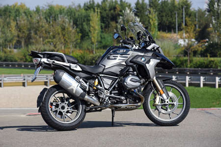 Side view of a German BMW R1200 GS motorbike or motorcycle parked on asphalt in the countryside in summer sunshine