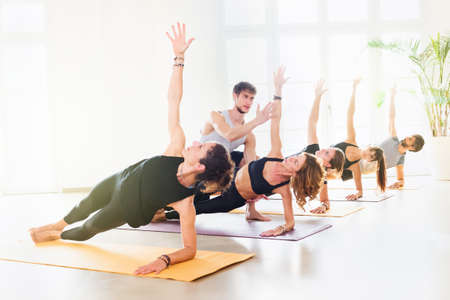 Modern yoga class doing side plank with the assistance of young male trainer. Group of people exercising in bright spacious studio. Side portrait against bright light of windows