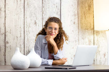Beautiful woman working from home with a laptop looking in the camera
