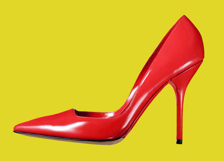 Single elegant stylish red leather ladies court shoe with a high stiletto heel viewed sideways isolated on yellow Standard-Bild