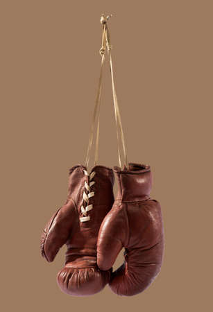 Isolated vintage boxing gloves hanging against brown background
