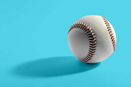 Close up of single leather cowhide baseball with red stitching over blue background